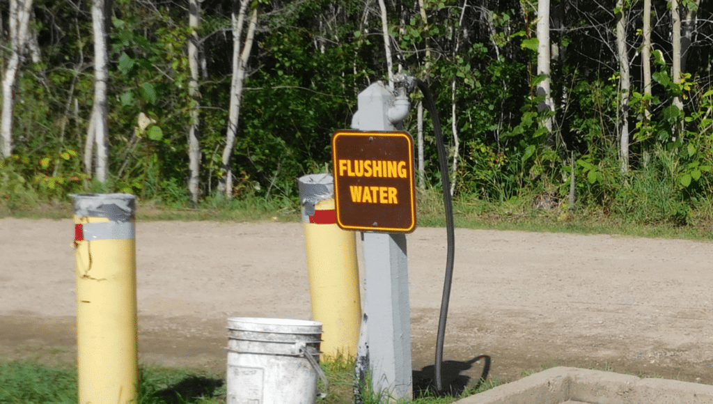 An RV dump station with the flushing water location labeled to clean the best RV portable waste tank.