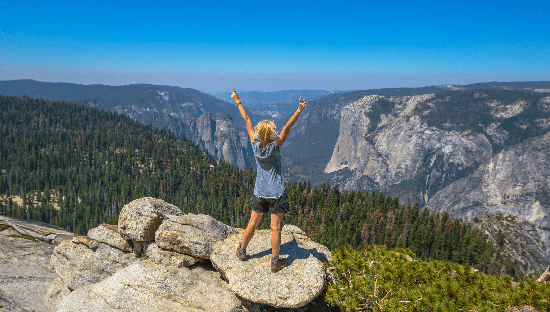A female hiker stands on a large rock in a valley, surrounded by mountains in Yosemite National Park. She has her hands held high above her head in awe of the view.