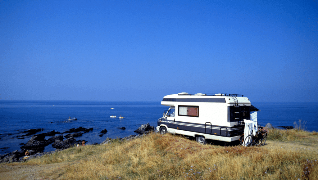 A motorhome is boondocking on a grassy overlook next to the ocean. The water and sky are deep blue. There are bicycles parked behind the motorhome and towels are hung up to dry.