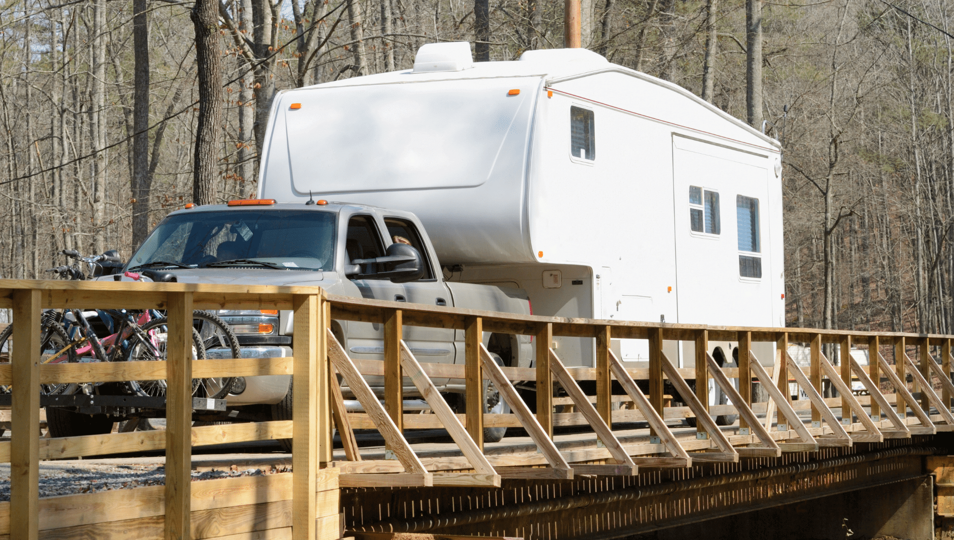 A fifth wheel RV is being towed by a pickup truck across a wooden rail bridge.