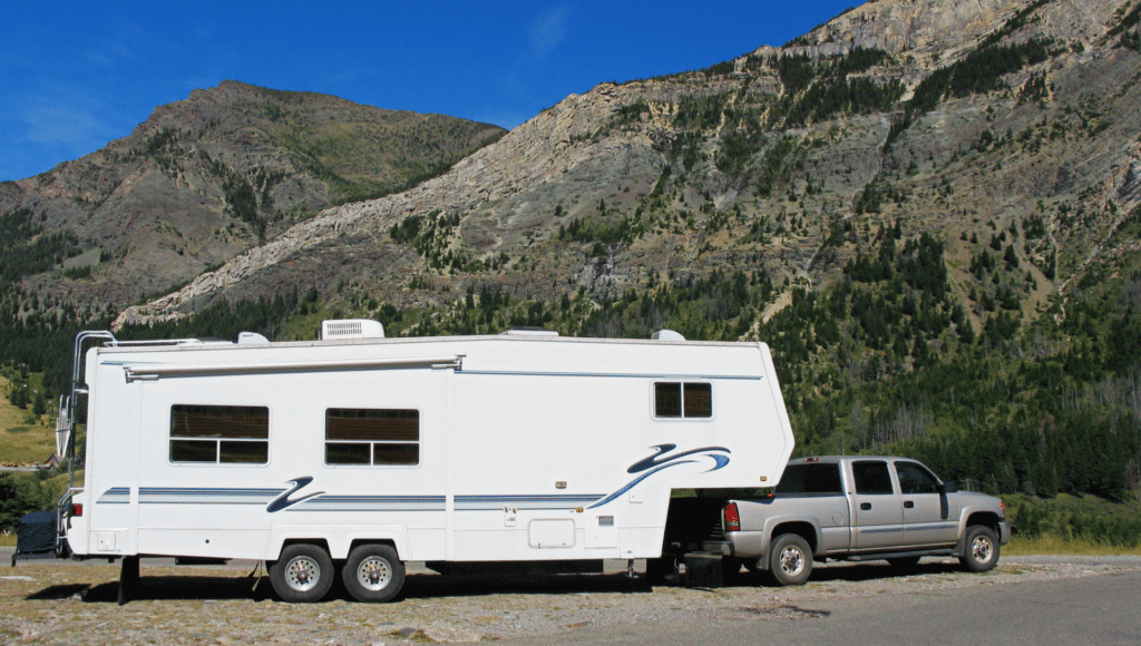 A pickup truck is connected to a fifth wheel RV using a 5th wheel hitch. It is parked in front of mountains with clear blue skies.