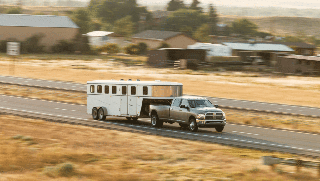 A four door pickup truck tows a livestock trailer down the highway utilizing a gooseneck hitch.