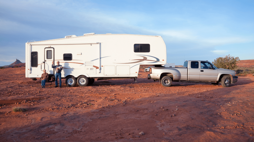 A large truck is hauling a trailer RV and is parked in the middle of the desert. A couple and their dog are smiling and waving sitting in front of their RV, excited for their dry camping experience.