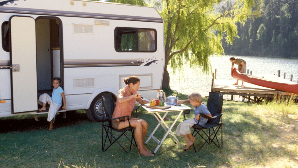 A family is sitting in front of their RV that is parked alongside a lake. The daughter is sitting in the doorway of the RV, Dad is setting up the kayaks on the lakeshore, and mom and son are sitting at the outdoor table setting up snacks.
