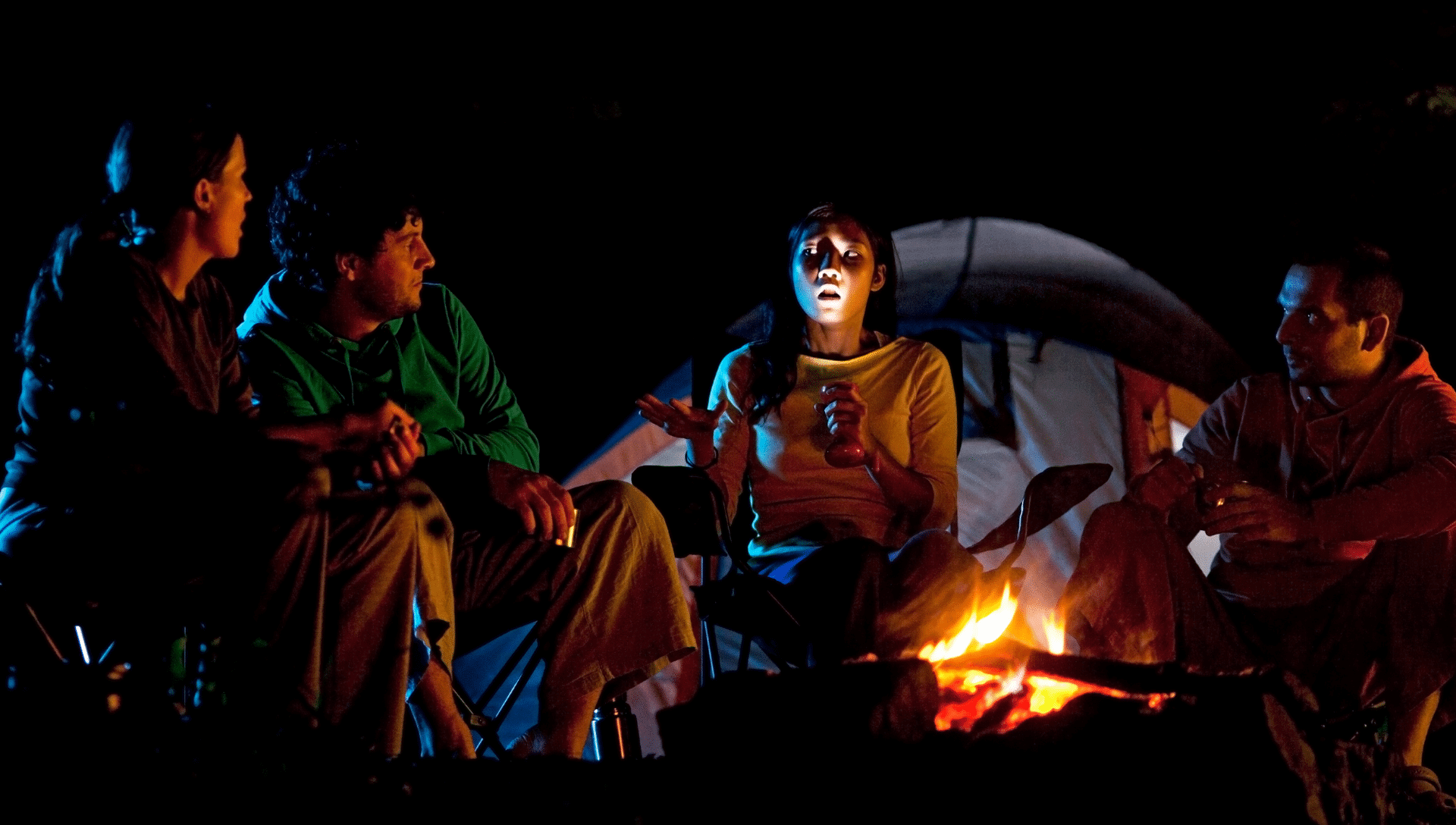 On a dark night, around a campfire, four people sit in chairs telling the best scary stories. The storyteller holds a flashlight, shining it from below on her face.