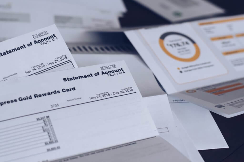 Pile of bills and credit card statements. You need to think about the debt coming with you on the road when asking yourself does living in an rv save money.