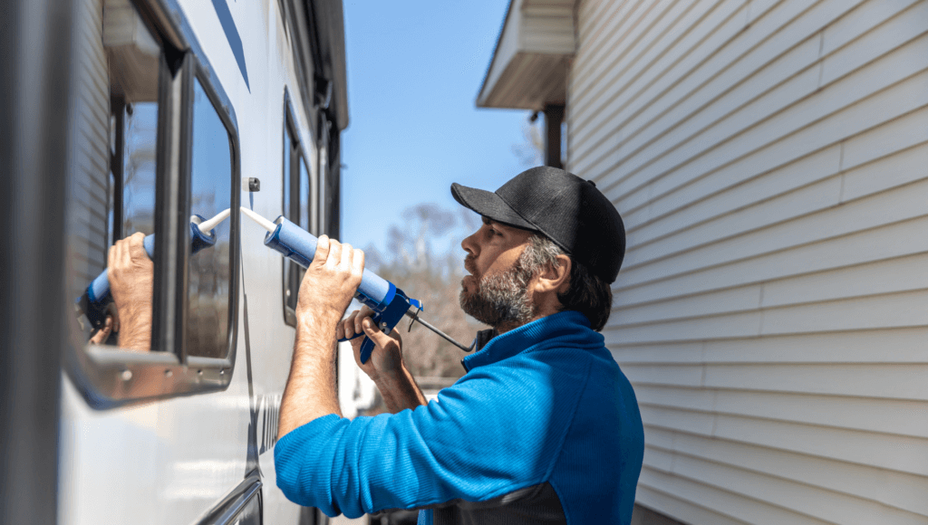 A man stands outside an RV while calking the RV window to prevent RV water damage repair.
