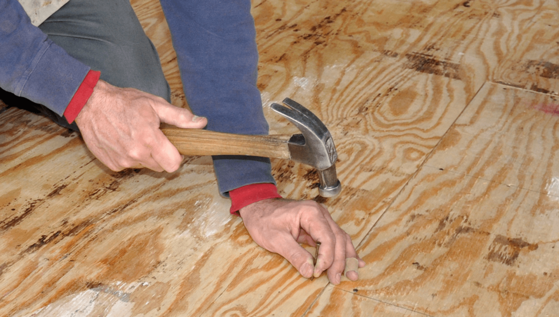 A man is using a hammer to nail in boards during an RV floor repair.