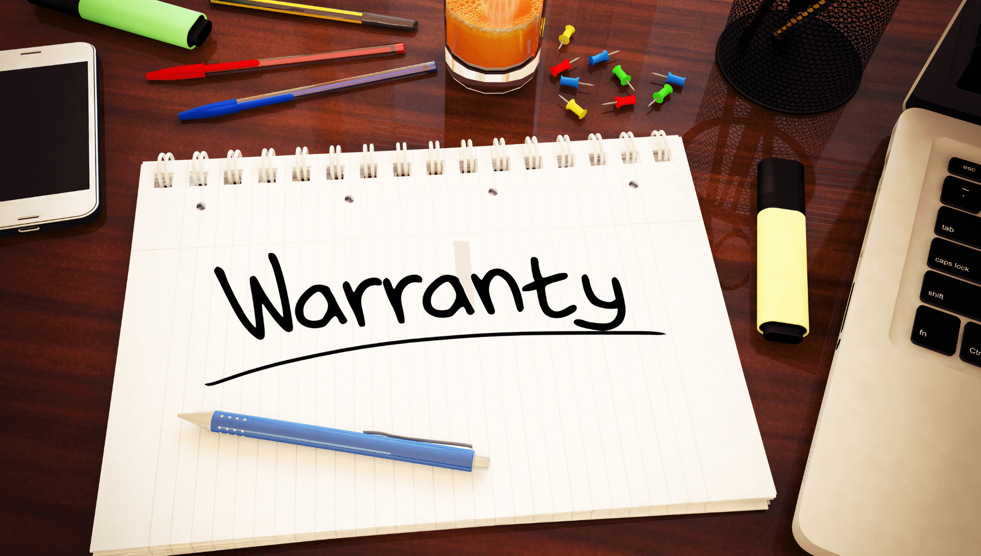 A notepad is on a desk with the work warranty written with black marker. On one side is a laptop and on the other side is a cell phone.