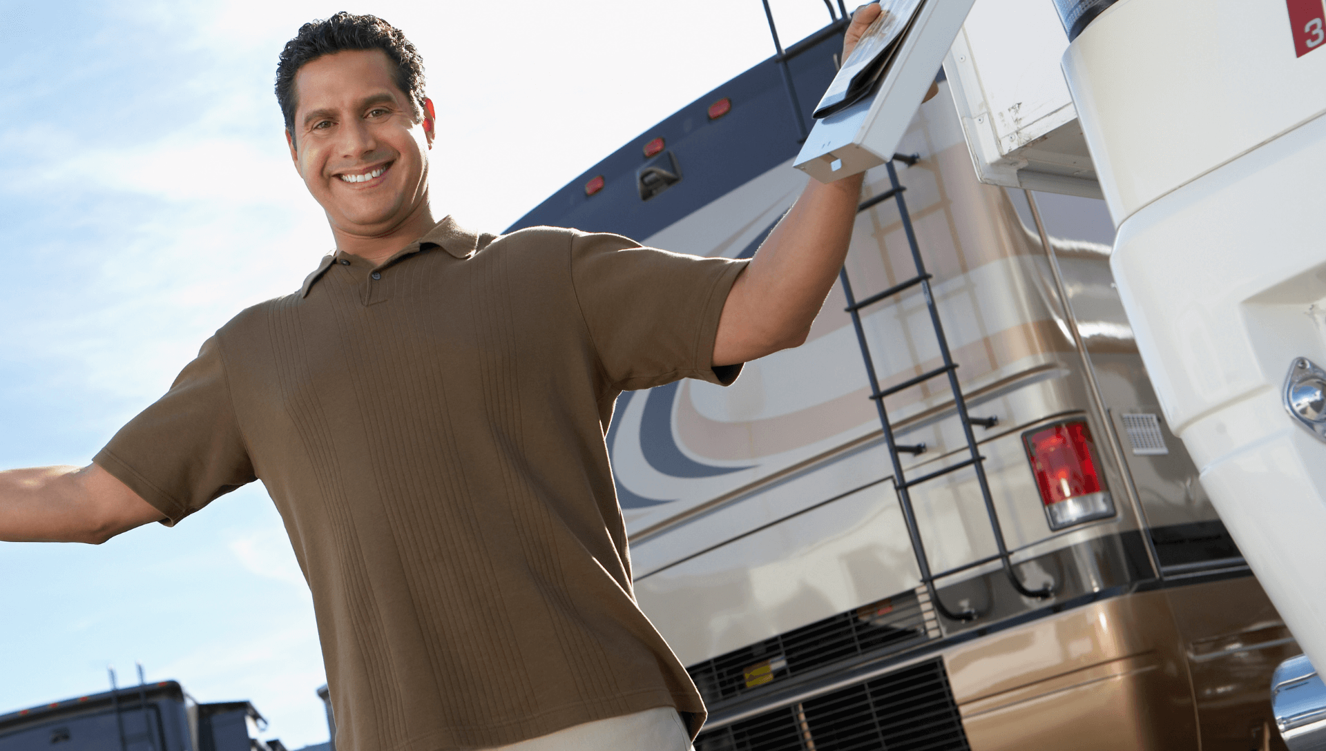 A man stands on an RV lot with a smile and his hands up declaring he found the best RV. He is standing behind a Class A motorhome.