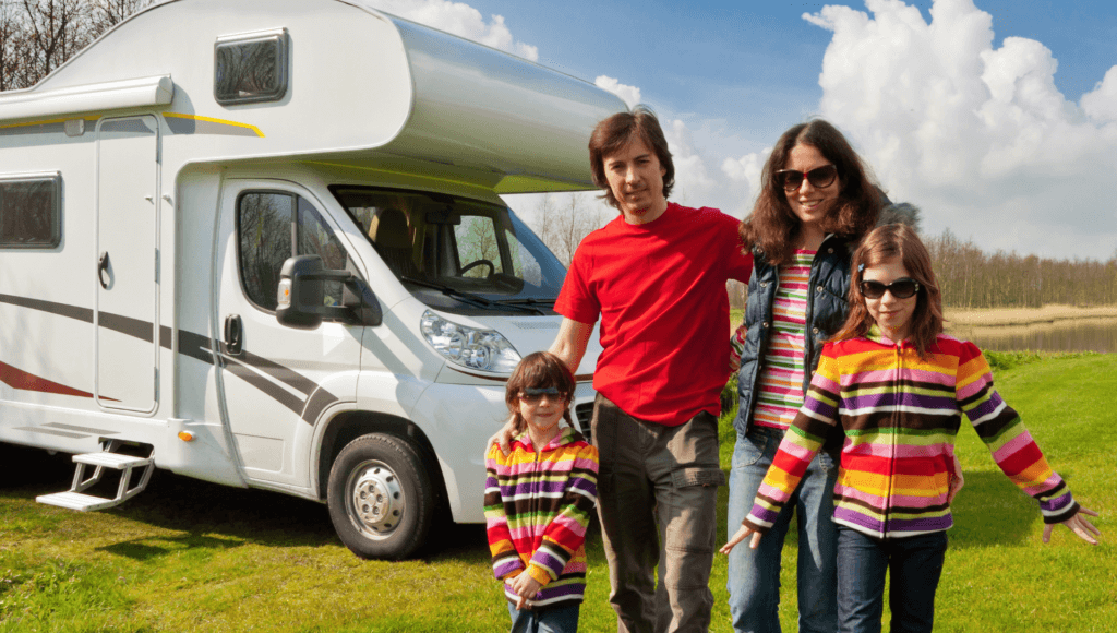 A father, mother, and two daughters stand in front of their Class C motorhome in a grassy area next to a lake with blue skies. They chose the best RV for their family.