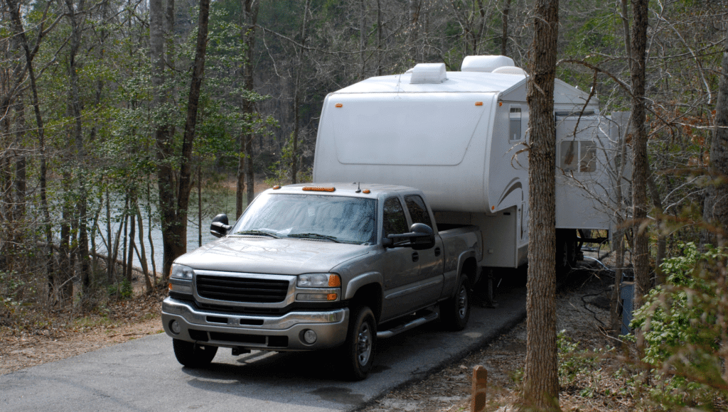 A fifth wheel is parked on a campsite near a lake in the woods with the pickup truck still attached to the RV.