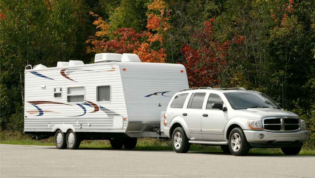 A silver SUV tows a travel trailer on a road with fall foliage in the background.