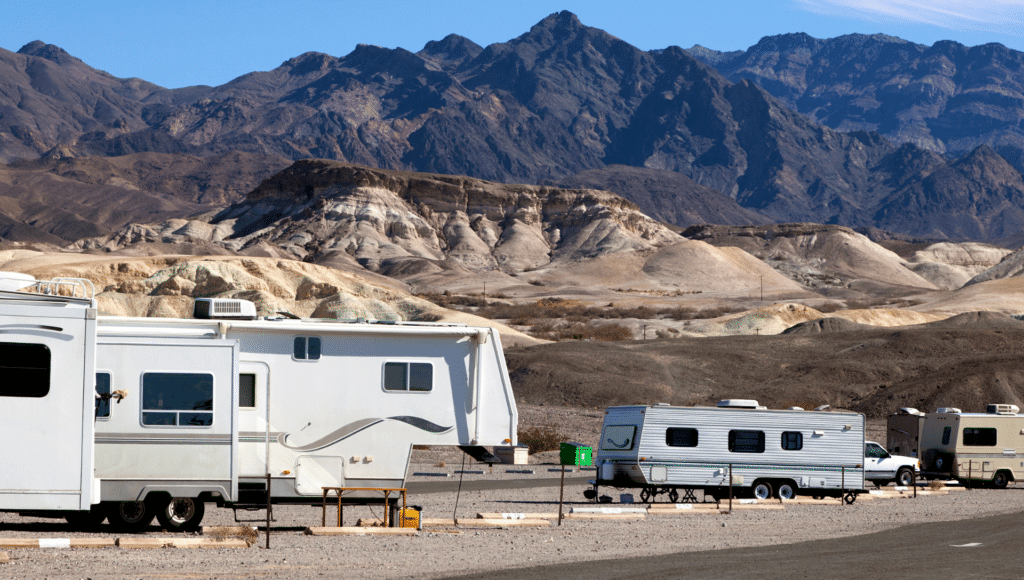 At the base of a large mountain range sits a camground with campers on site. This shows a variety of RVs including 5th wheel vs travel trailer.