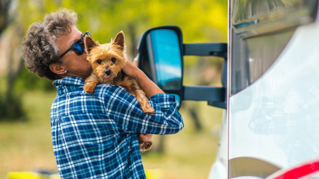 Older woman with short pepper gray hair in blue plaid shirt holds yorkie dog outside of RV. An RV temperature monitor creates a safe environment for the pets to be left alone in the RV.