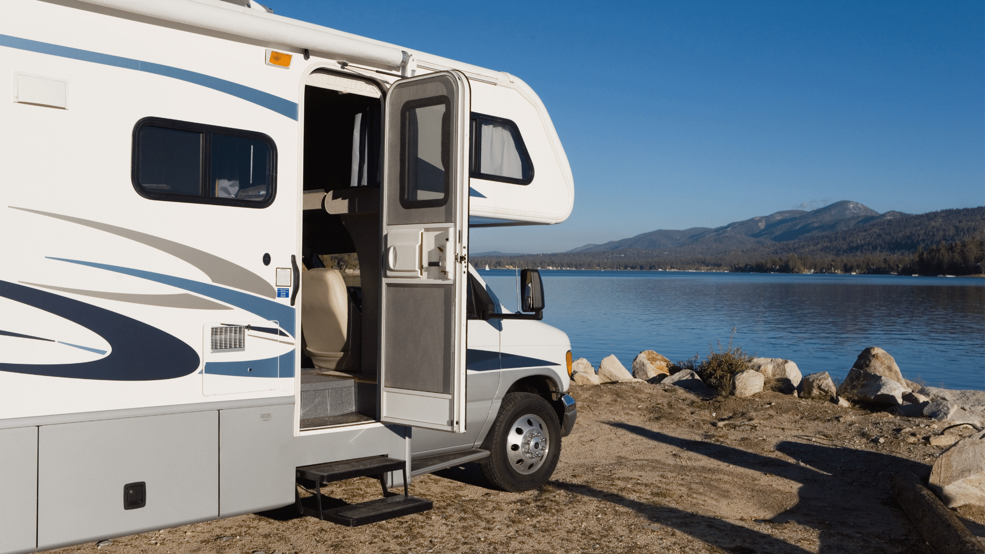 RV parked near a lake on a sunny day. Does living in an RV save money?