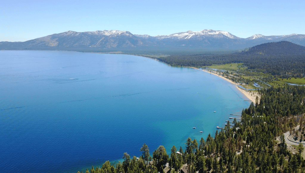 An aerial view of Lake Tahoe with trees in the foreground and mountains in the background. Boats are in the blue water of the lake.