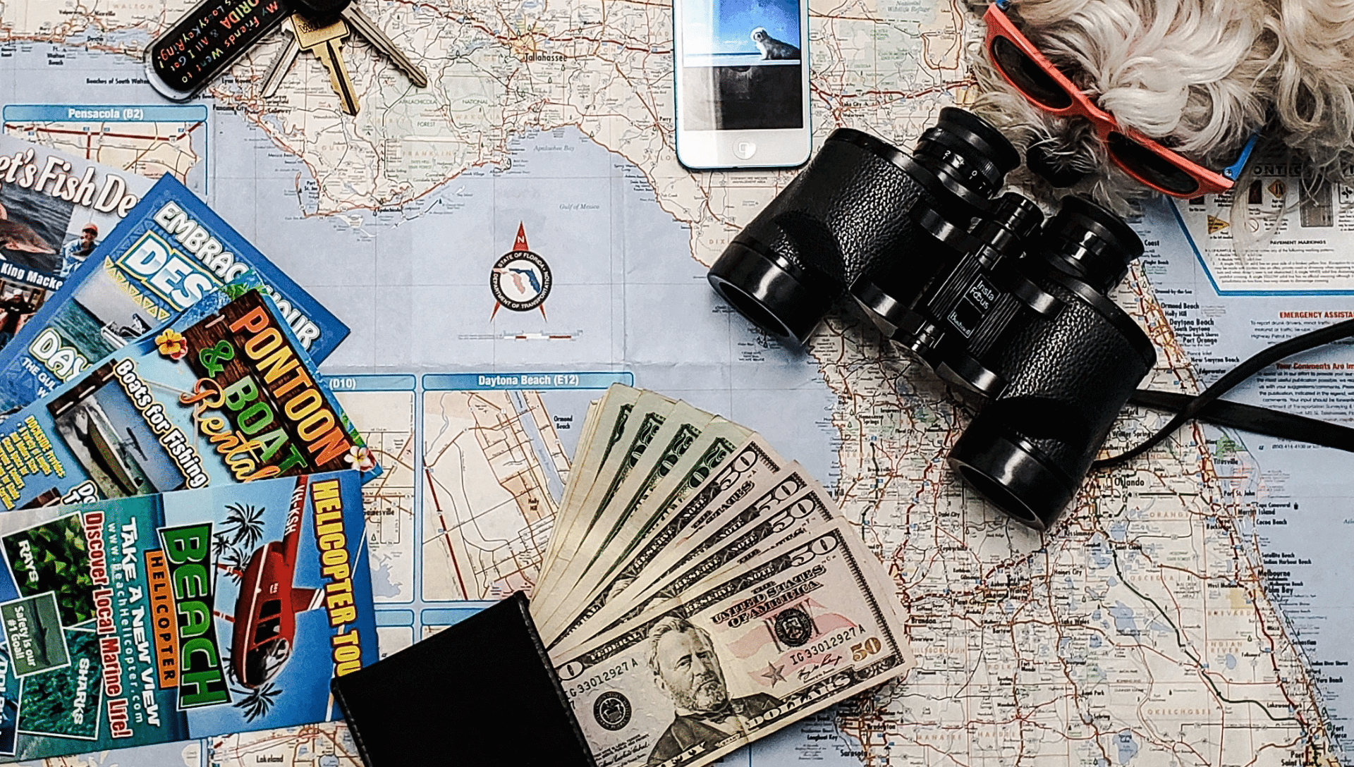 A United States map is laid out on a desk. On top of the map is cash money, attraction brochures, keys, and binoculars while planning how to save money on a road trip.