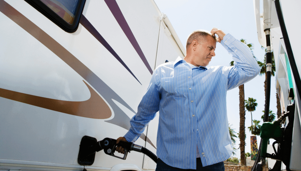 A man is at a gas station pumping gas into his RV. There are palm trees in the background. The man is scratching is head thinking about how to save money on a road trip.