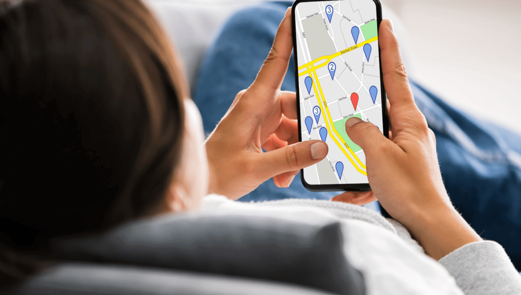A woman is sitting on the couch at home looking at her phone that has a map on it while she is road trip planning.