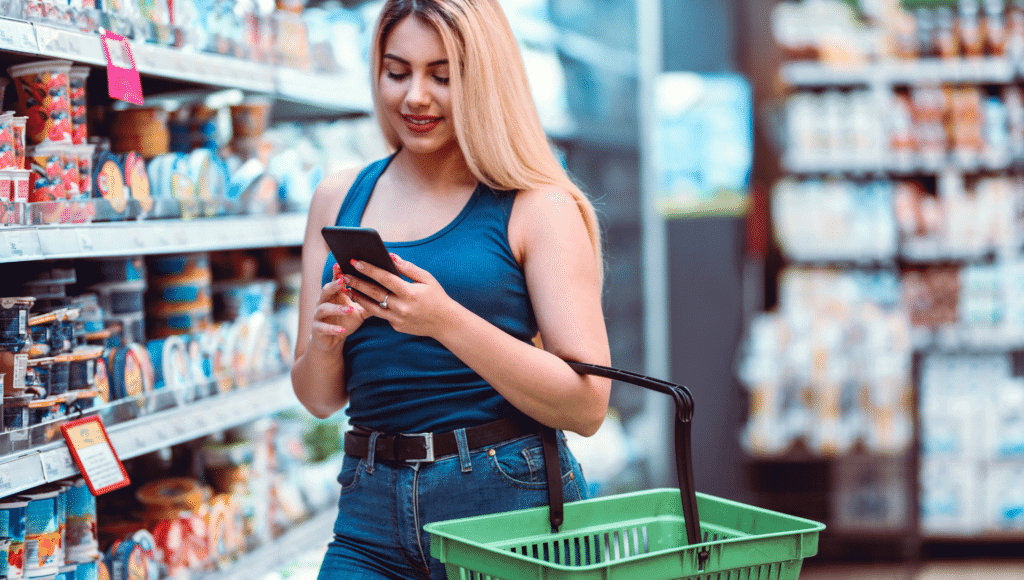A young woman walks through a grocery store with a shopping basket on her arm. She is looking at her phone to compare prices which is one of the ways to save money on a tight budget.