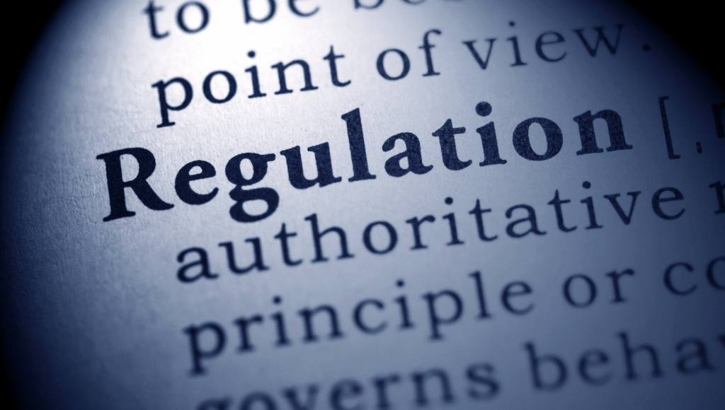 An up close view of a dictionary page defining the word regulation.