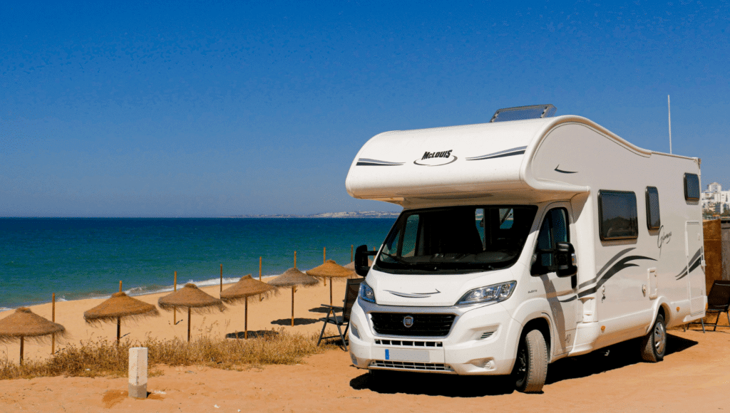 A motohome is parked along a beach with a blue ocean and blue sky. A motorhome vs a travel trailer is easier to pull up and park somewhere like this.