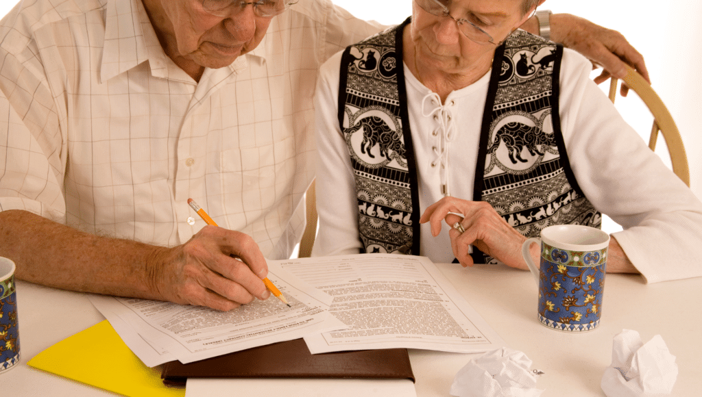 An older couple sit at their kitchen table, with coffee, while reviewing their RV loan paperwork and considering all costs of RVing.