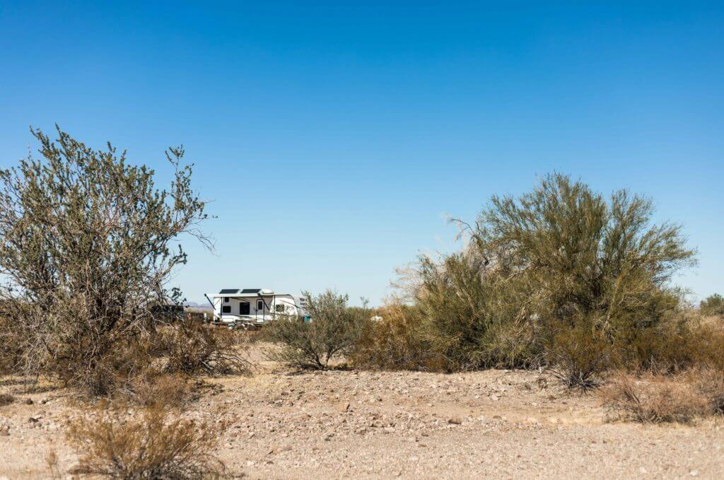 Travel trailer in the distance with sand and big bushes surrounding it. To get off grid you'll need some boondocking must haves.
