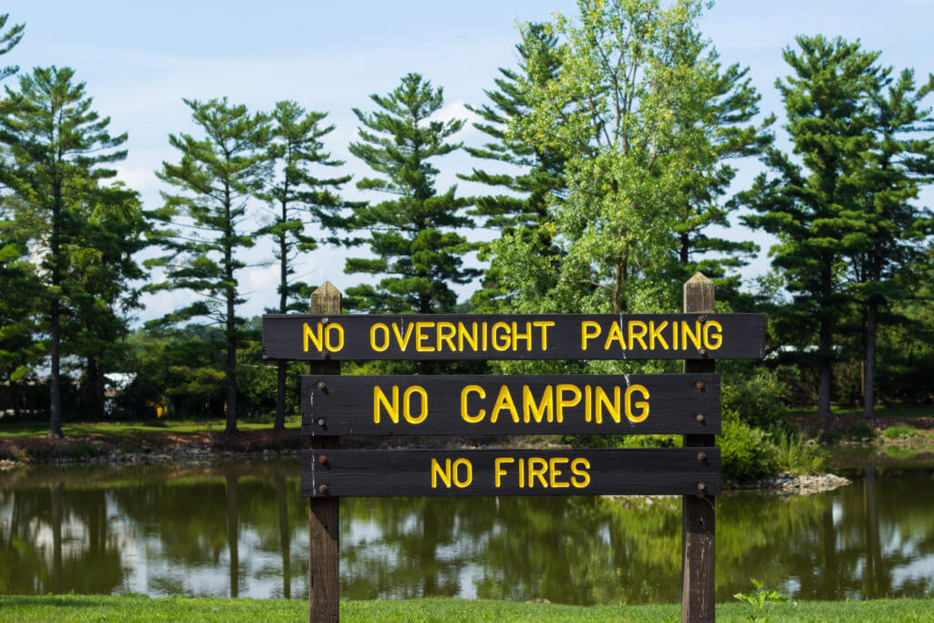 Sign in front of a lake that says no overnight parking, no camping, no fires. Obeying the signs is following BLM Boondocking rules.