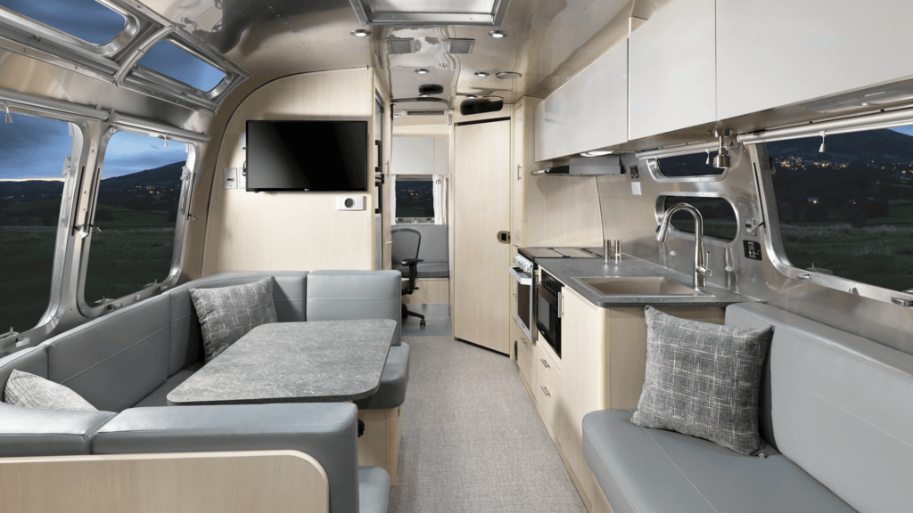 Airstream Flying Cloud 30FB Office internal view of the kitchenette and living area with large windows outside.