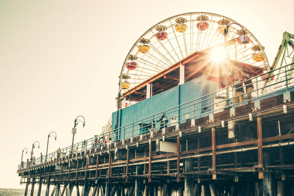 Picture of the sun shining through the ferris wheel on the Santa Monica Pier. Santa Monica is  the perfect romantic California getaway for Valentine's Day.