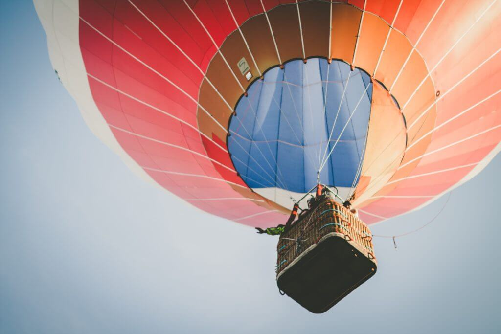 Shot of a red and blue hot air balloon from underneath as it floats away.