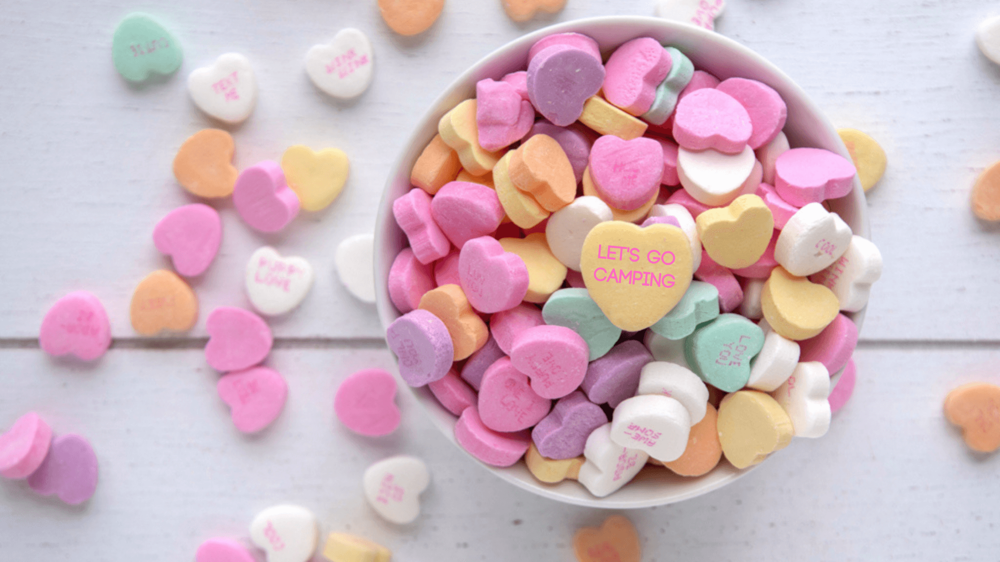 "bowl of candy hearts on a table with the top candy saying ""let's go camping"". This covers Valentine gift ideas"