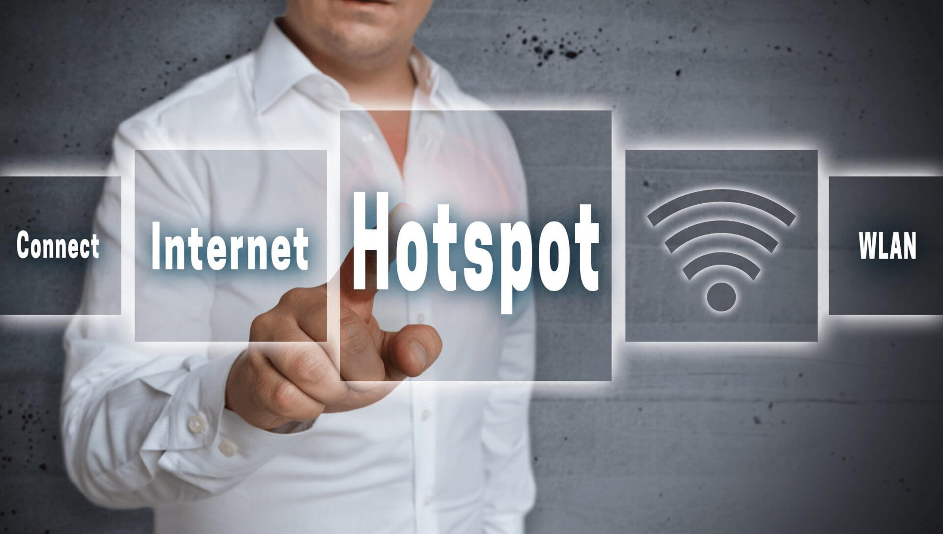 A business man stands behind a clear board with the word hotspot in the middle which he is pointing to. It has other boxes stating internet, WLAN and connect and also has the wifi bar signal indicator.