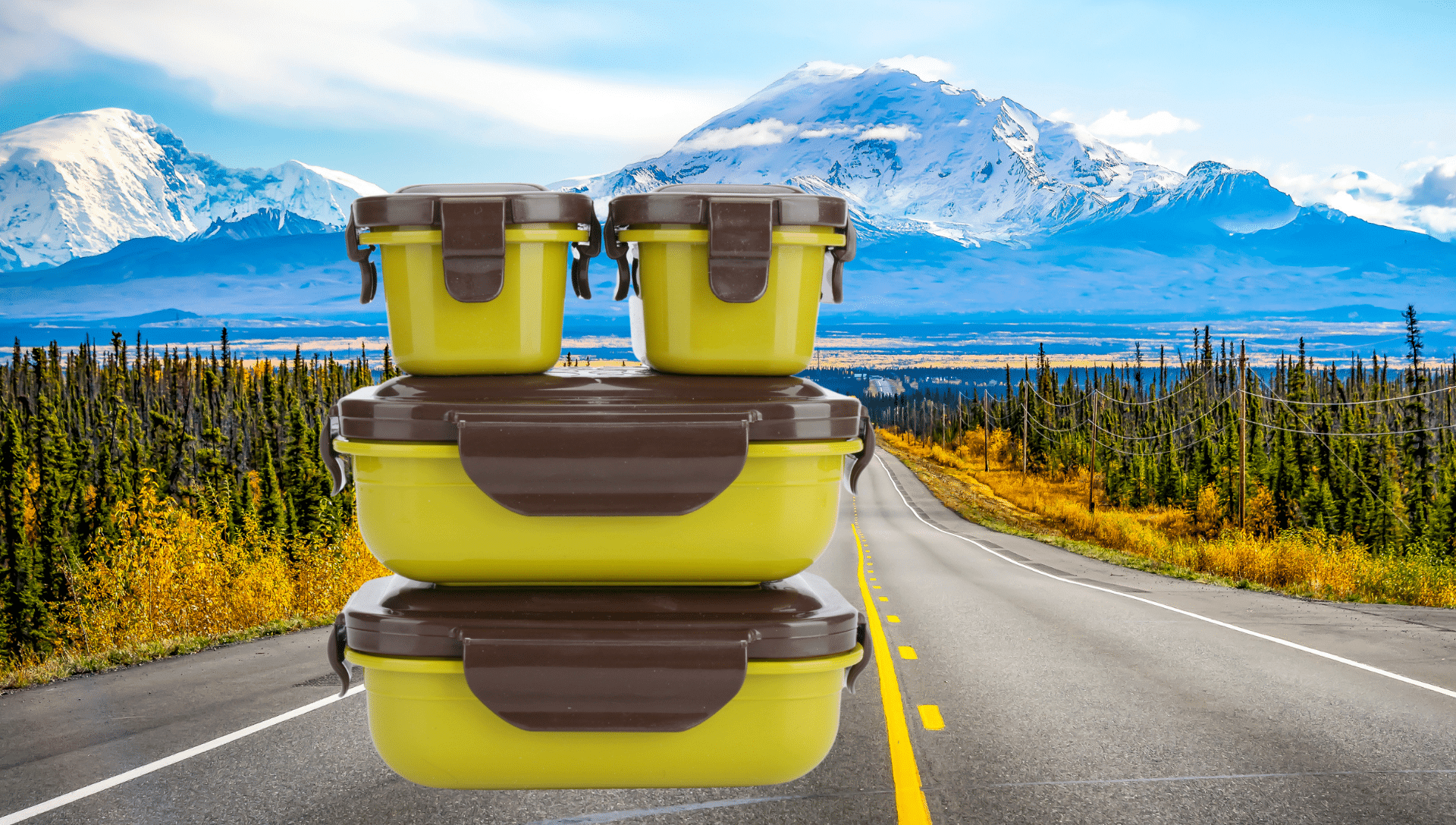 Plastic snack containers are stacked and situated in front of a roadway backdrop with mountains. These containers contain healthy road trip snacks.