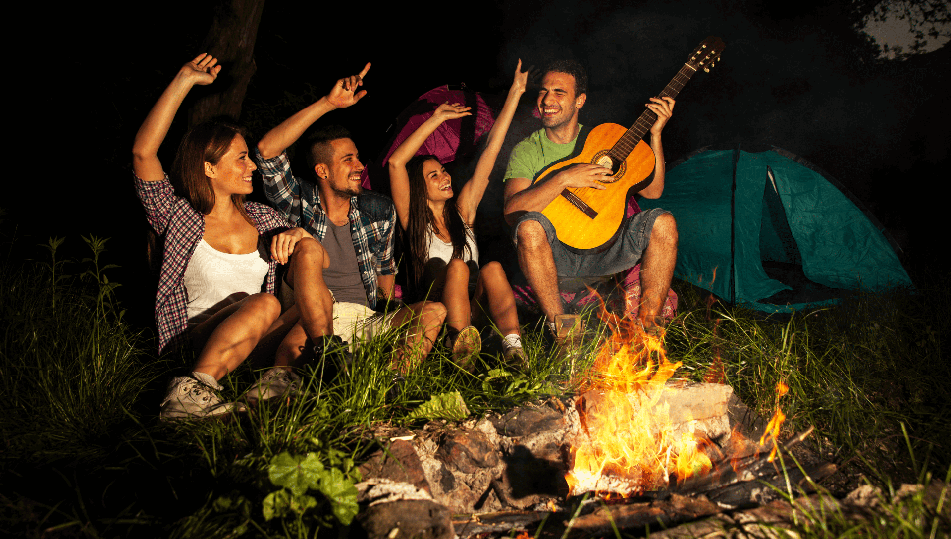 Four adult friends sit by a fire while singing campfire songs. One is playing the guitar and the others have their hands in the air while singing along.