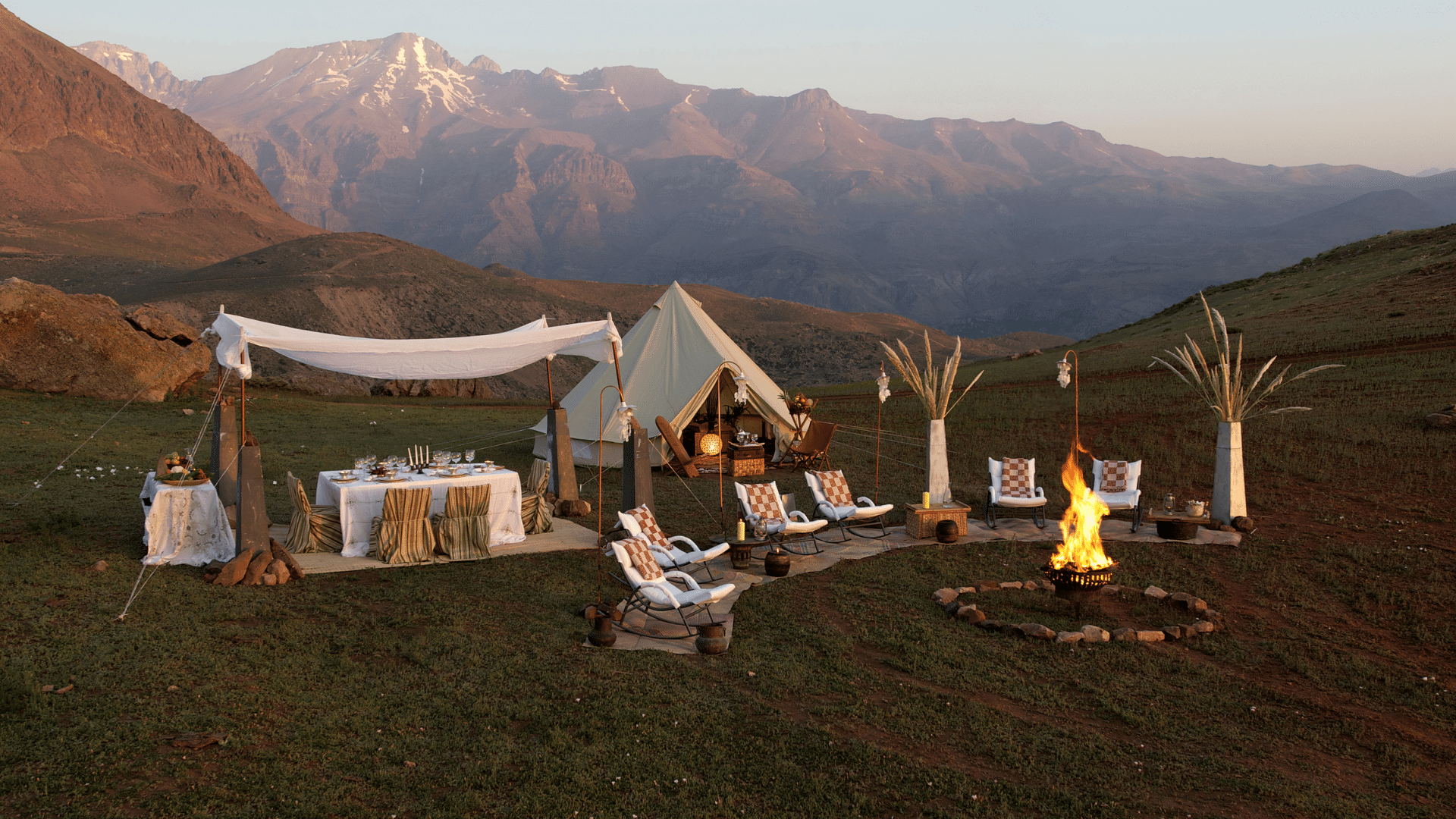 Glamping set up among the mountains at sunset. There is a nice dinner set up with a white table clothed setting and wine glasses ready to be filled. A fire pit surrounded by six luxurious and comfy looking lounge chairs. And a large yurt like tent with all the expected glamping luxuries inside like a bed and cozy lamps and blankets.