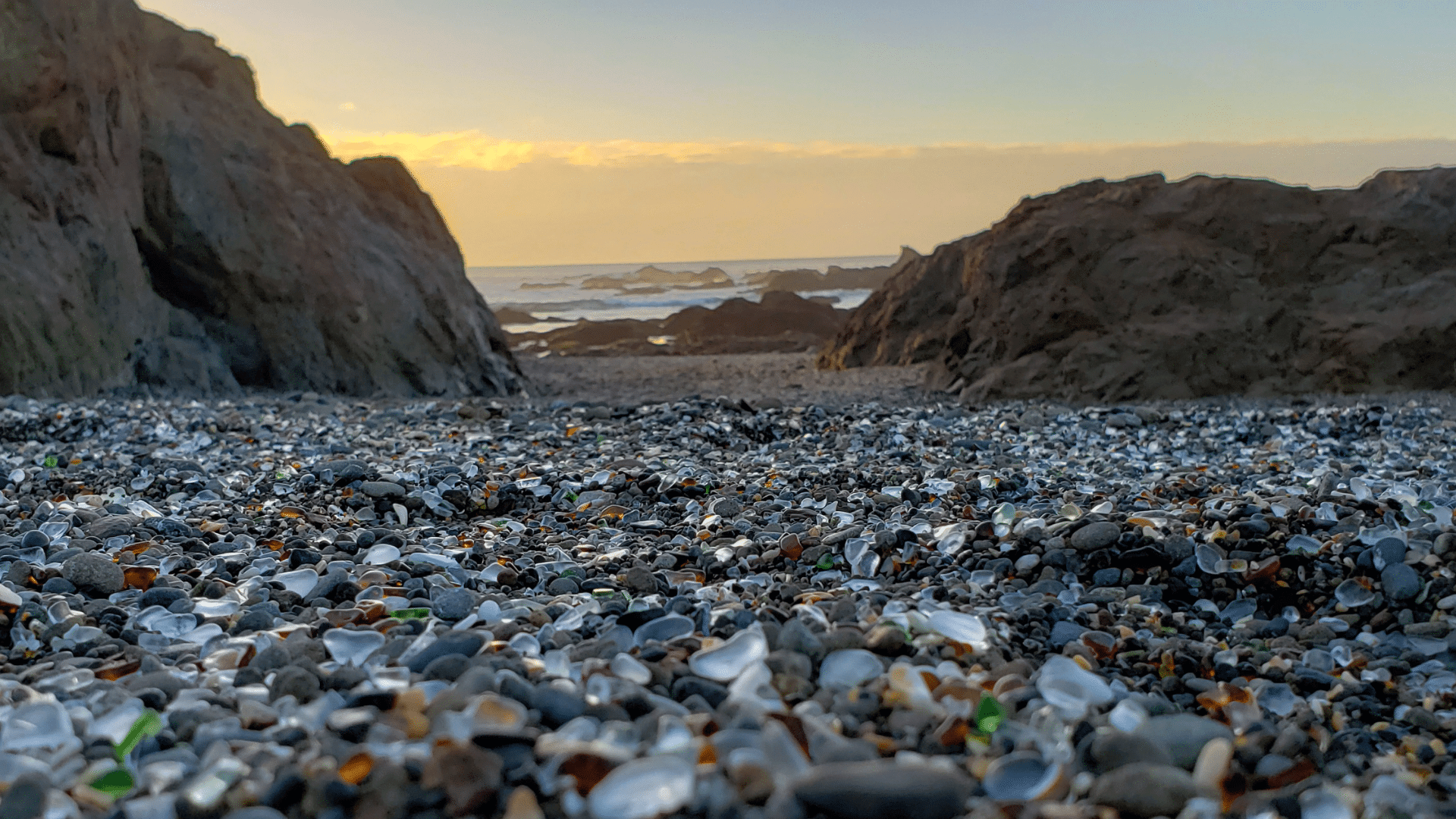 Sea glass on the beach in the forefront and cliffs and the ocean at sunset in the background in Fort Bragg,CA.