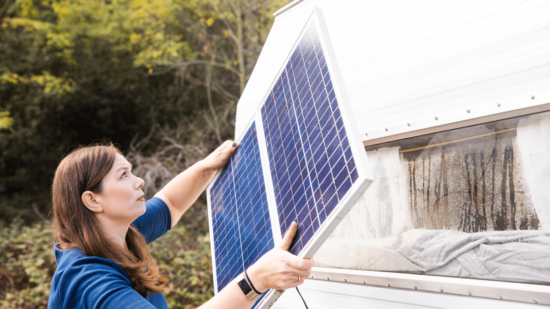 Woman with dark hair and blue shirt looks kinda confused as she attempts to install a solar panel on her RV. Her RV has dirty windows, but I don't think that's her main concern. She is likely installing the solar panel so she can power her RV's appliances and air conditioner.