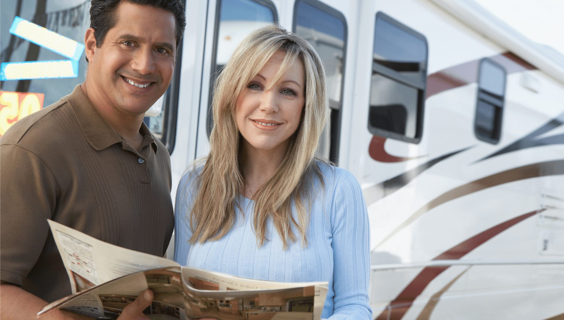 A smiling man and woman look at a brochure at an RV dealership, standing in front of an RV.
