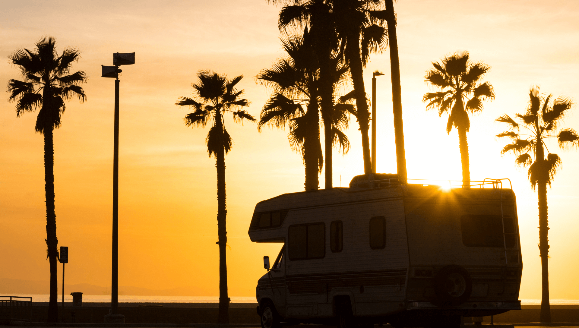 A motorhome is parked under palm trees beneath a bright orange and yellow sunset sky.