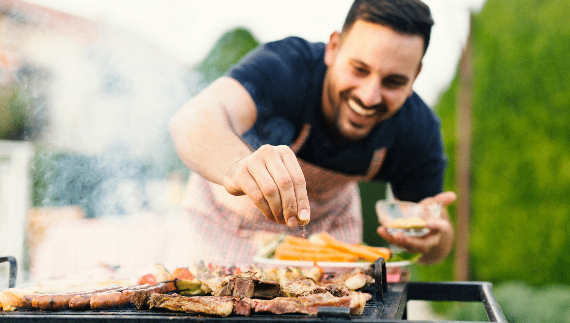 A smiling man leans over the grill as he adds seasoning to his food. Smoke is coming up from the grill.