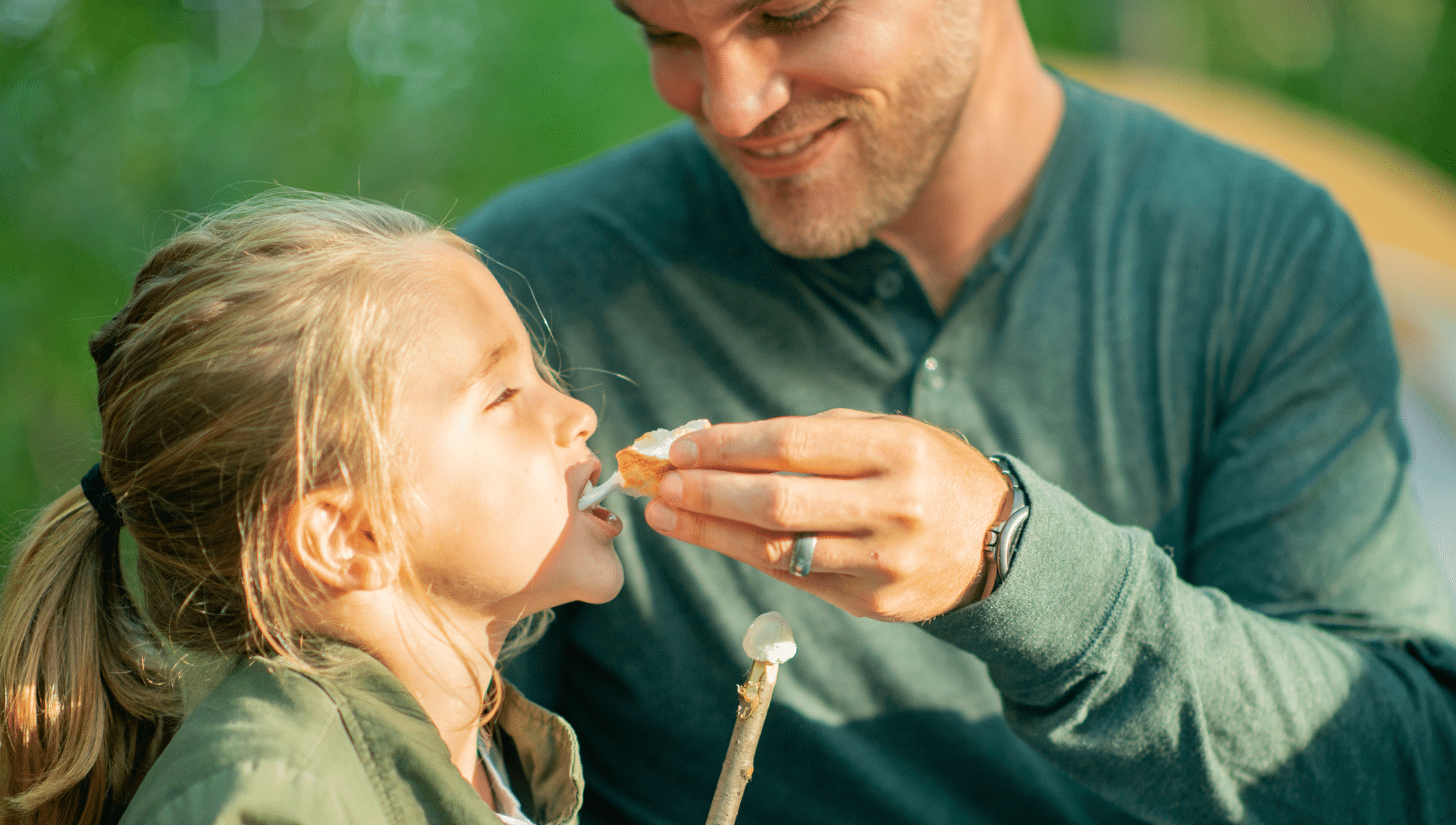 While camping, a father holds a roasted marshmallow while his daughter takes a bite of the gooey marshmallow she just roasted.