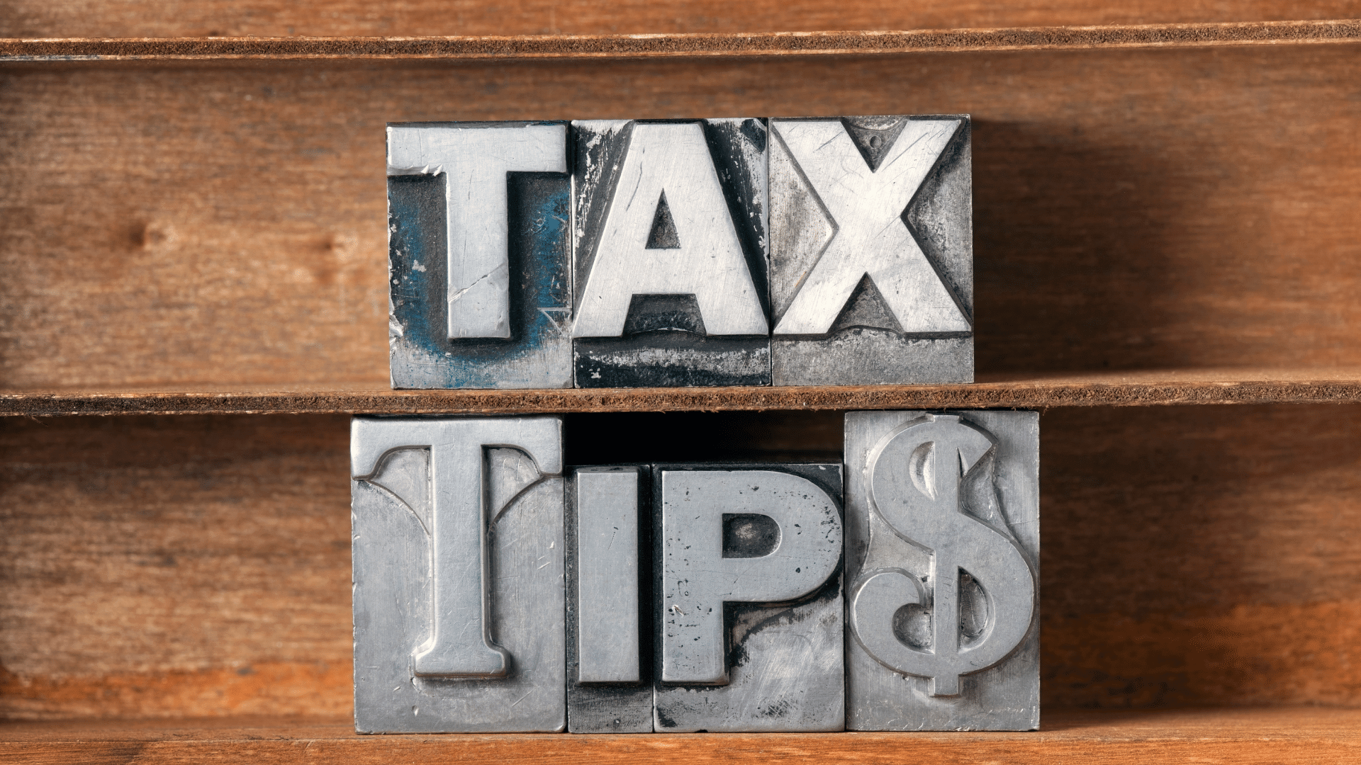 Tax Tip$ metal letter blocks set against a wood background. Helpful Tips for RV Owners on the Tax Benefits Available