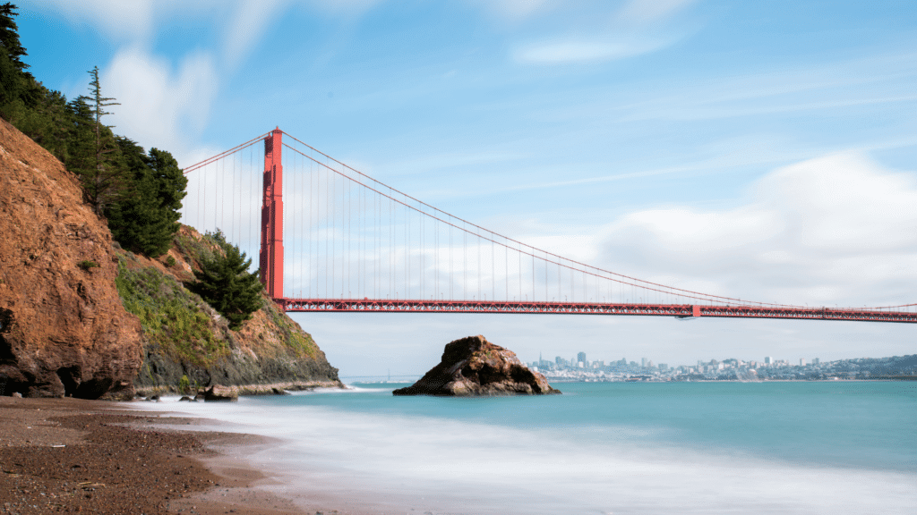 Kirby Cove beach with pine trees as San Francisco, the fog, and the Golden Gate bridge loom in the background.
