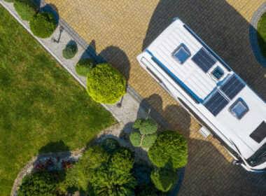 How to know how many solar panels for your RV? An aerial shot of a white RV with 3 solar panels on its roof is parked in a sunny driveway surrounded by grass and small hedges.
