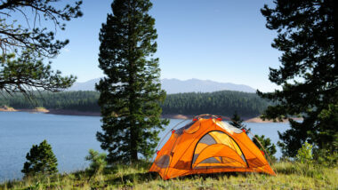 Orange tent camping under some pine trees above a lake with mountains in the background. Ultimate camping hacks to make camping that much better!