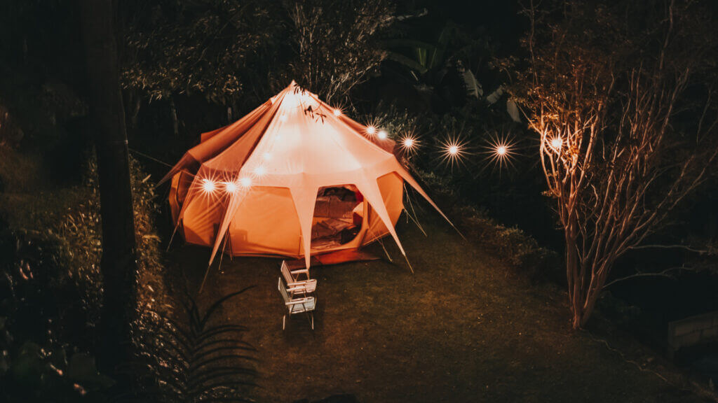 A campsite glows in the night thanks to string lights strung around the trees.