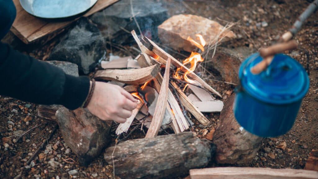 A hand with a match reaches into a fire to light it. There are already a few flames on the small fire, and a blue pot hangs above to soon be heated for breakfast.